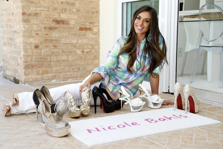 """Em uma manhã de sol, Nicole Bahls recebeu a reportagem do R7 em seu apartamento, localizado em um condomínio de luxo na Barra da Tijuca, na zona oeste do Rio de Janeiro. Sem cerimônias, a beldade abriu a porta de sua casa ainda de bóbis no cabelo.Com um sorriso no rosto explicou o motivo de se ter um tapete branco com a grafia de seu nome em rosa em sua porta. """"Assim não dá para errarem a porta [risos]. Esse tapete aqui eu mesma encomendei. Eu amo rosa. Se fazem com nome de edifício, queria um com meu nome também"""".Reportagem: Rodrigo Teixeira"""