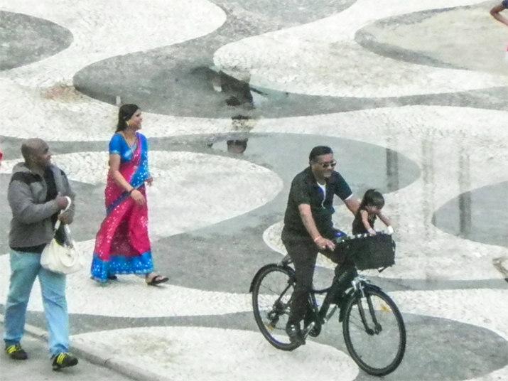 A menor mulher do mundo (em pé, na cestinha da bicicleta) despertou a curiosidade de quem passava pela praia de Copacabana, na zona sul do Rio, na tarde desta terça-feira (26).A indiana Jyoti Amge mede apenas 62,8 cm