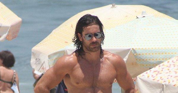 Com tanquinho de dar inveja, Marcos Pitombo vai à praia com amigos