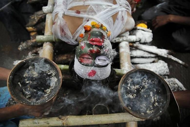 Um devoto hindu participa do festival hindu Shivrati, que acontece nesta quinta-feira (27) na Índia. Simulando um funeral, ele celebra Shiva, deus hindu da morte e da destruição