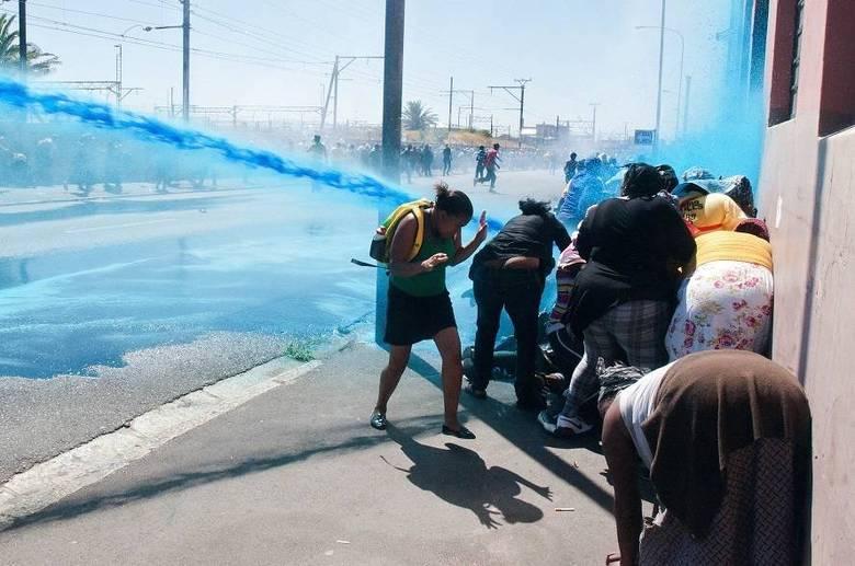 Civis são atingidos por um canhão de água e granadas disparadas por membros das forças policiais da África do Sul enquanto participavam de um protesto contra a falta de saneamento nesta quinta-feira (27).  Os manifestantes tentavam chegar ao centro da Cidade do Cabo