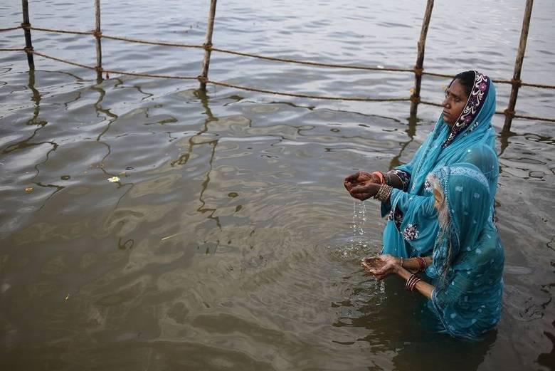 Mulheres hinduístas oferecem orações ao deus Shiva no encontro do rio Ganges com o rio Yamuna, durante o festival Shivrati