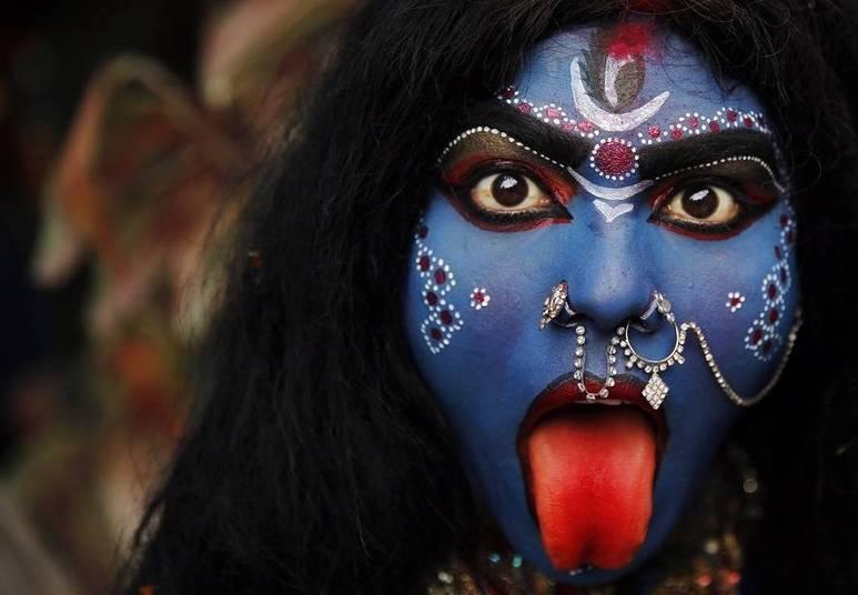 Uma mulher, vestida como a deusa hindu Kali, participa da procissão no Festival Shivrati