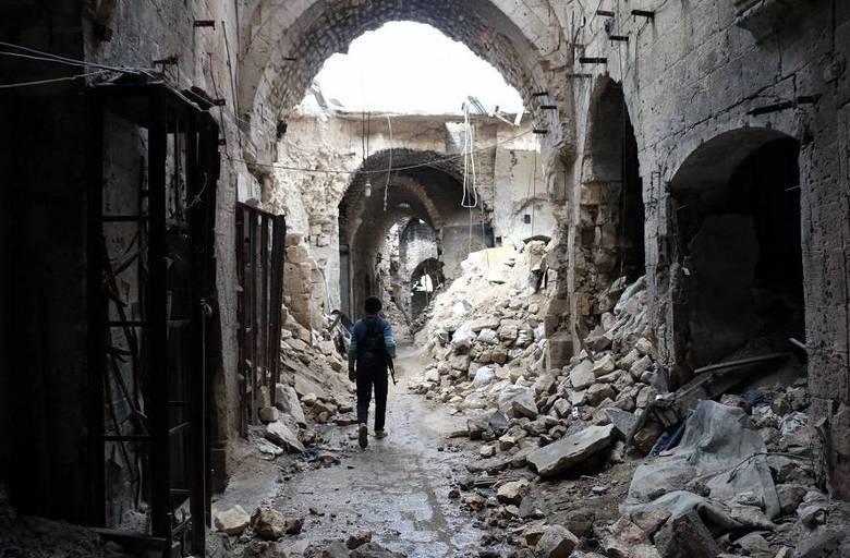 Um combatente caminha em um beco devastado do antigo mercado de Aleppo, no norte da Síria