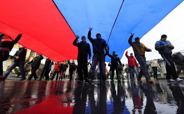 Manifestantes favoráveis a Rússia esticam uma bandeira russa para reunir seus militantes no centro de Simferopol, na Ucrânia