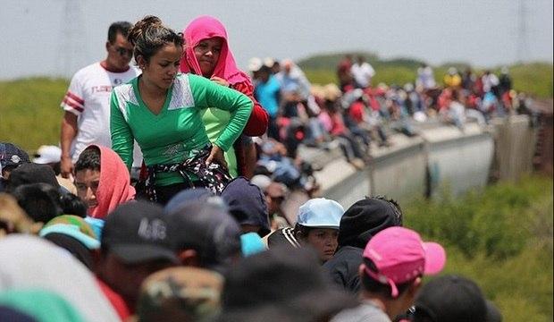 Imigrantes ilegais se equilibram em trem de carga para chegar aos EUA