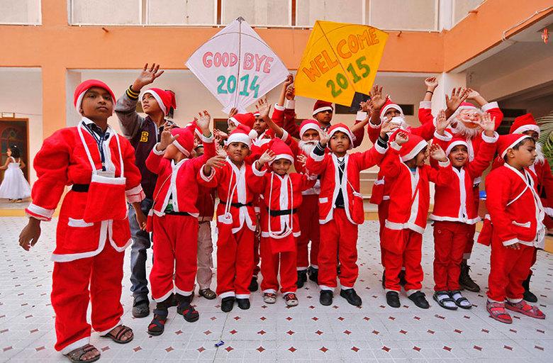 Alunos vestidos com roupas de Papai Noel posam para foto durante celebração do Ano Novo em escola deAhmedabad, na Índia, nesta quarta-feira (31)