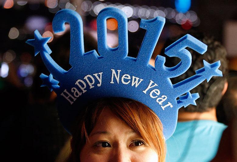 Mulher usa chapéu para comemorar a chegada de 2015 enquanto espera a chegada de 2015 na Austrália nesta quarta-feira (31)
