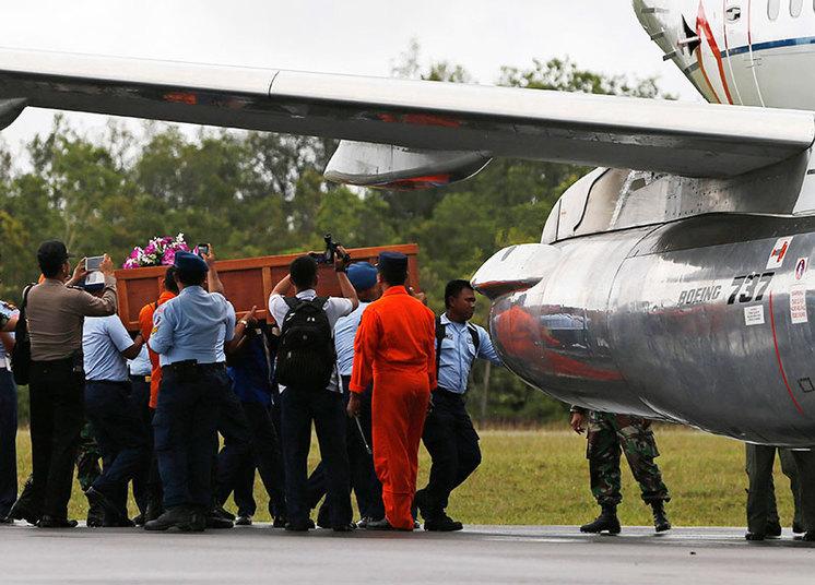 Na Indonésia, a festa deu lugar à tristeza com o resgate de corpos do mar após a queda do avião da AirAsia. Na foto, soldados da Força Aérea da Indonésia carregam urna com corpo de passageiro do voo QZ-8501, da AirAsia, na base de Iskandar em Pangkalan Bun. Vítimas estão sendo levadas a Surabaya, na Indonésia