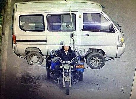 Chinês carrega van sobre triciclo no meio de avenida movimentada