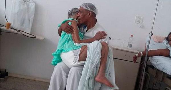 Imagem de maqueiro acalentando idosa em hospital de Salvador ...