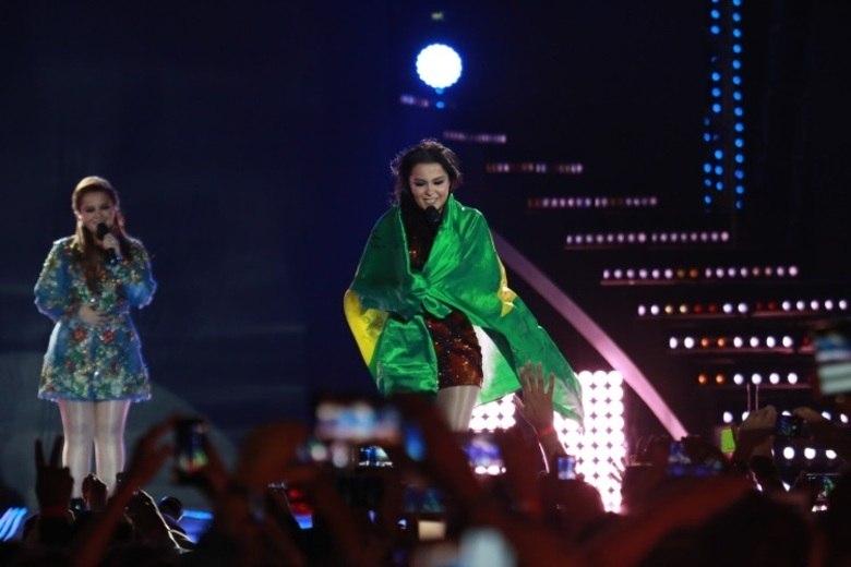 Emocionadas, elas até usaram uma bandeira do Brasil no show