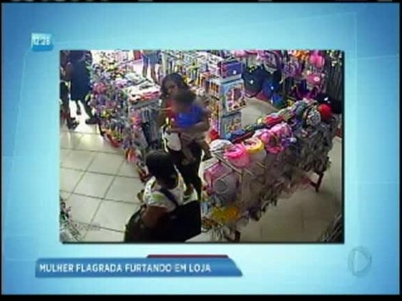 Mulher com criança no colo é flagrada furtando loja em Salvador; assista