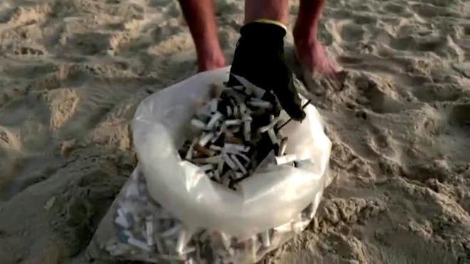 Artista israelense coletando pontas de cigarro da praia para suas obras