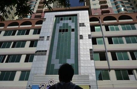 Homem observa fachada de prédio com janelas destruídas pelo terremoto