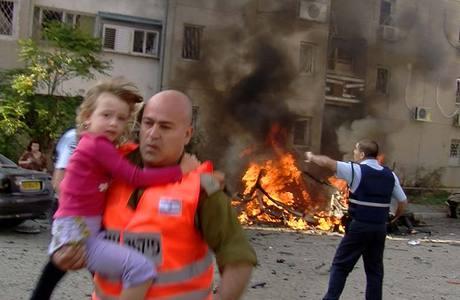 Soldado israelense retira criança de prédio atingido por míssil palestina em Beersheva, na terça-feira passada (20)
