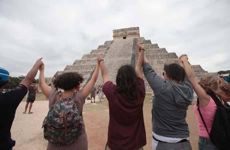 Turistas erguem as mãos para o alto em frente à pirâmide de Kukulkan, no Estado mexicano de Yucatan