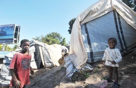 Crianças haitianas em frente às tendas onde moram em Canape-Vert: mais de 360 mil pessoas ainda vivem nessa situação, quase três anos após o terremoto