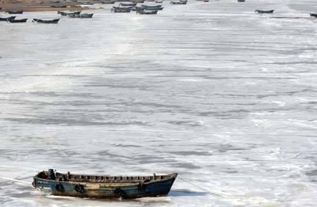 Barcos de pesca nas águas congeladas na baía Jiaozhou
