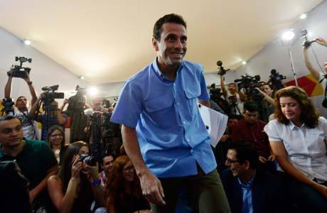 Henrique Capriles chega para coletiva em Caracas, em sala lotada de jornalistas