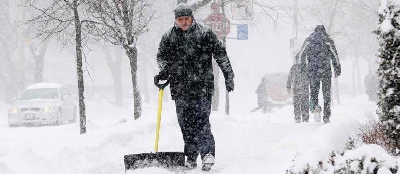 Homem limpa calçada após nevasca em Boston