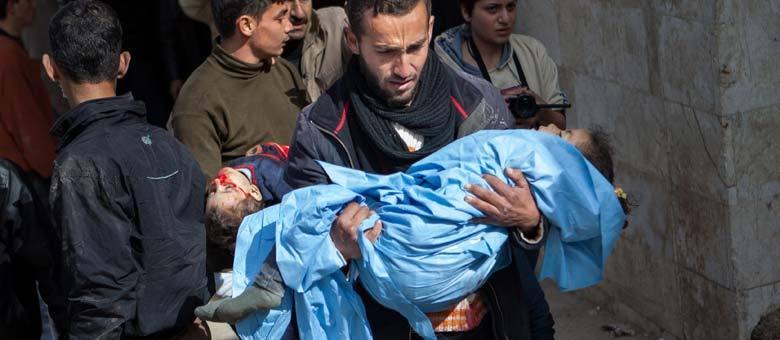 Em Kfar Nubul, parentes carregam corpos de irmãos de 5 e 2 anos de idade que foram mortos após um ataque aéreo perpretado pelo governo na cidade de Hass, na Província de Idlib
