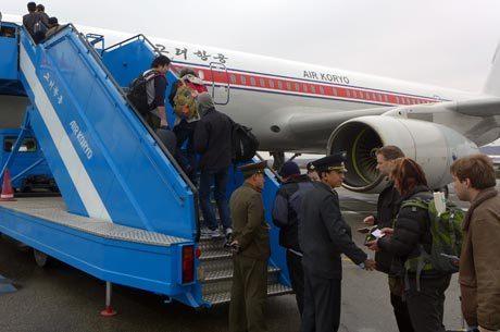 Imagem da AFP mostra autoridades norte-coreanas revisando os passaportes de um grupo de estrangeiros