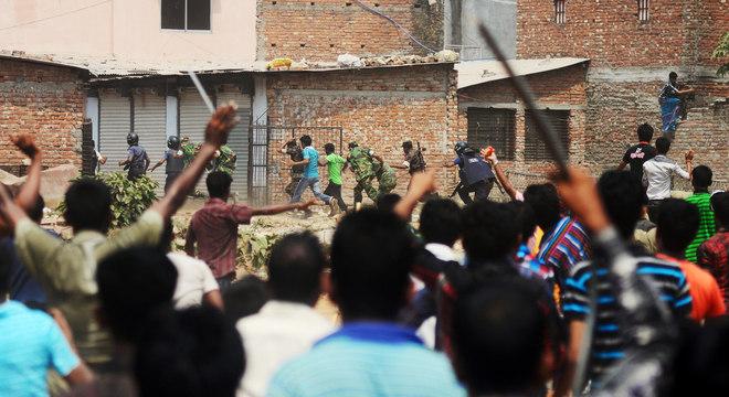Policiais e membros das Forças Armadas correm de multidão enfurecida próximo ao local da tragédia
