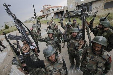 Na imagem, combatentes das tropas governistas comemoram a vitória em Haydariyah