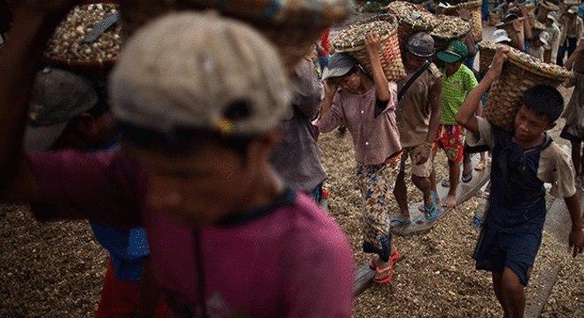 Crianças trabalham como adultos carregando cestos cheios de pedras em Mianmar