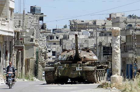 Homem passe de moto ao lado de tanque de guerra destruído em Homs