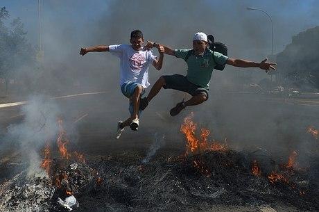 Manifestantes pulam barreira de pneus em chamas durante protesto contra realização da Copa em frente ao Estádio Nacional de Brasília