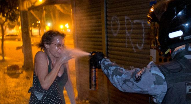 A mulher desarmada tentou se proteger com a mão do banho de spray de pimenta que levou do policial