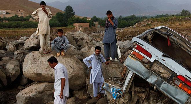 Afegãos observam carro destruído após inundações no distrito de Dara Shakar, em Cabul. Pelo menos 22 pessoas morreram após fortes chuvas que caíram no sábado (10)