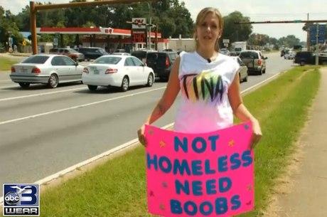 """Com um cartaz escrito """"Não sou desabrigada, preciso de seios"""", Christina Andrews tenta conseguir ajuda para pagar implantes de silicone"""
