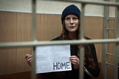 """Brasileira Ana Paula Maciel segura cartaz durante audiência na corte de Murmansk, Rússia: """"Eu amo a Rússia, mas me deixem ir para casa"""""""
