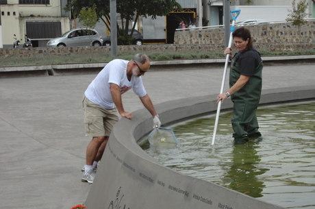 Beto e Therezinha durante limpeza do espelho d'água