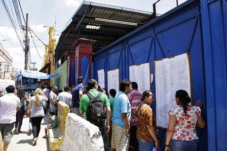 Comerciantes verificam lista com os nomes, colocada em um dos portões da Feira da Madrugada