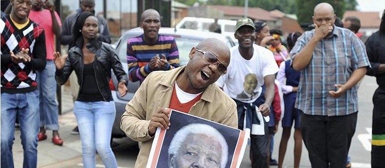 Pessoas cantam e dançam em Vilakazi Street, na cidade de Soweto