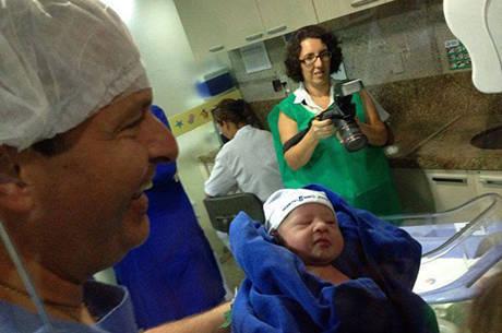 Eduardo Campos sorri ao segurar o filho recém-nascido Miguel