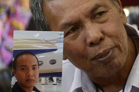 Selamat Omar mostra foto do filho, Mohd Khairul Amri Selamat, que estava a bordo do voo MH-370