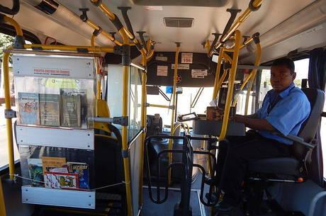 Cobrador monta estante para os livros diariamente no ônibus em que trabalha