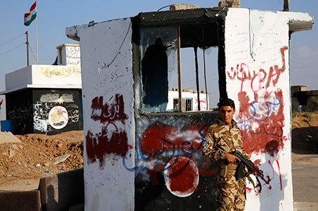 Combatente curdo aparece em um dos locais recuperados na vila de Barznki