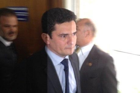 Imagem de Sergio Moro recebe o efeito das luzes dos flashes dos fotógrafos quando ele se dirigia à comissão do Senado