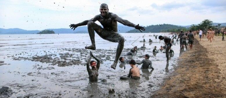 Foliões brincam na lama em Paraty, durante o Carnaval; depois da festa, grupo desfila pelas ruas da cidade