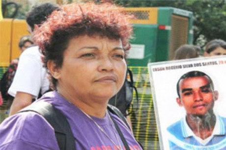 Débora da Silva com cartaz do filho Edson dos Santos, morto em maio de 2006