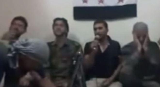 Rebeldes aparecem nas imagens segurando rifles e cantam com um microfone