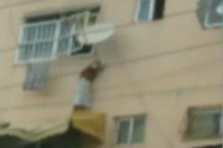 Criança ficou em cima de um toldo e segurando na antena de TV