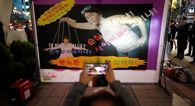 Cartazes de manifestantes que pedem a renúncia da presidente sul-coreana mostram imagens dela sendo manipulada pela amiga Choi Soon-sil