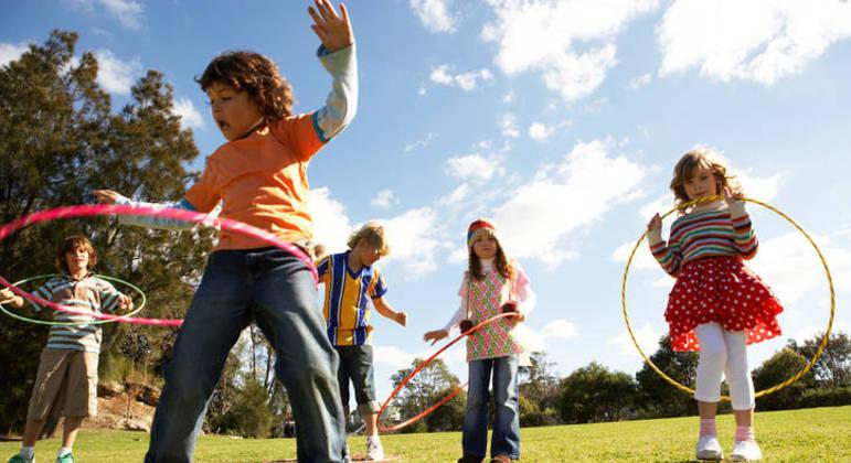Crianças brincando de bambolê no parque